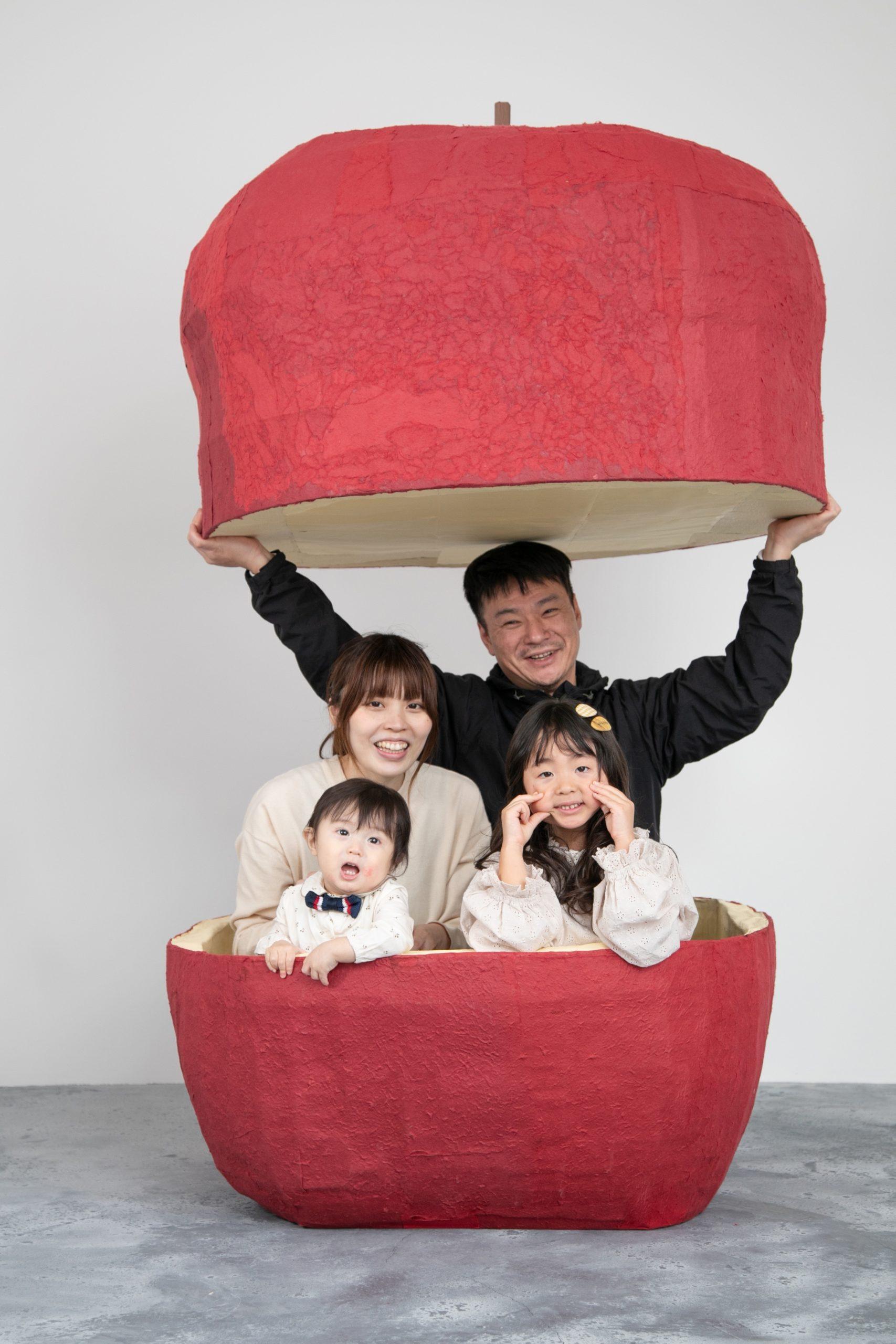 巨大りんごの中で家族写真